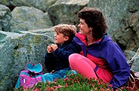 mother and son at rest in mountains with heather foregroumd, Whistler, British Columbia, Canada