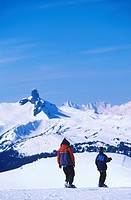 snowboarders atop peak with Garibaldi Mountain and black tusk beyond, Whistler, British Columbia, Canada