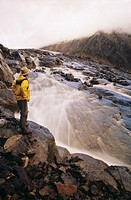 Hiker beside alpine creek, Hudson Bay mountain, Smithers, British Columbia, Canada