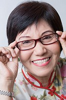 Portrait of a senior woman adjusting her eyeglasses and smiling