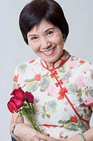 Portrait of a senior woman holding a bunch of rose and smiling