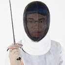 Portrait of a male fencer wearing fencing mask and holding a fencing foil