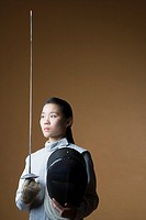 Close-up of a female fencer holding a sword and a fencing mask