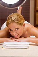 Germany, young woman lying on massage table