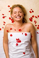 Germany, young woman lying on massage table, petals on chest