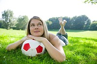 Woman 20-25 lying in field, leaning on football, close-up
