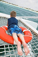 Young Boy Laying on Lifesaver on Catamaran