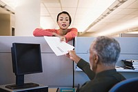 African businesswoman handing paperwork to coworker