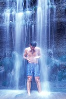 Man Standing in Waterfall