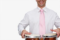 Mid section view of a businessman playing bongo and smiling