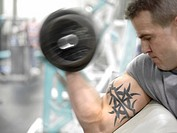 Tattooed Caucasian Man Lifting Weights In Gym