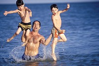 Dad Lifting Laughing Boys Out Of Ocean