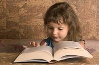 Young Girl Reading From A Big Book