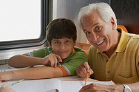 Portrait of a senior man teaching his grandson and smiling