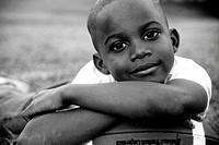 African American Boy Resting His Head On A Football And Smiling At You