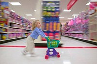 Toddler Pushing A Play Shopping Cart Along The Toy Aisles
