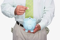 Mid section view of a man putting a coin into a piggy bank