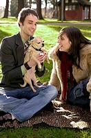 Contemporary Urban Couple Playing With A Puppy In The Park
