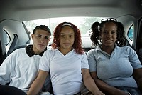 Teenaged friends sitting in back seat of car
