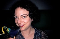 Caucasian Woman Drinking A Martini With A Lemon Twist