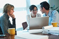 Two businesswomen and a businessman discussing in an office