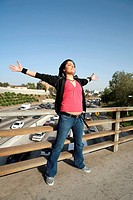 Young woman standing on an overpass with her arms outstretched