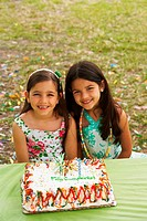 Two girls sitting in front of a birthday cake