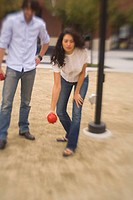 Young Woman Tossing Bocce Ball