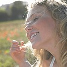 Close-up of teenage girl 16-17 sitting in meadow with eyes closed