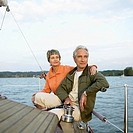 Mature couple on sailing boat on lake, man holding rudder