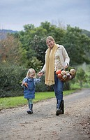Mother and daughter 3-4 walking on dirt road carrying basket with food, woman looking at camera