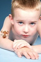 Boy 8-9 lying down with insect crawling on arm, portrait, close-up