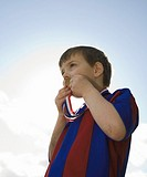 Boy 5-7 in soccer kit kissing medal, pictured against sky, low angle view