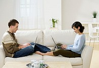 Young couple sitting face to face on sofa, using laptops, side view