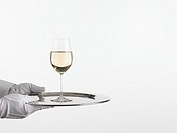 Waiter holding tray with glass of white wine