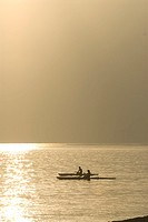 Silhouette of people canoeing in sea