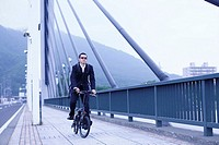 Businessman in Sunglasses Biking on a Bridge
