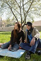 Couple with a map and compass in a park smiling (thumbnail)