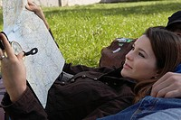 Woman smiling holding map reclining on sleeping man in a park
