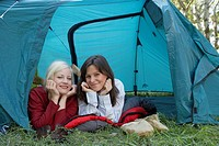 Two women lying in a tent at campsite smiling