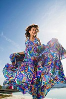 Dynamic beauty woman laughing outdoors in a colorful long summer dress