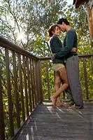 Couple outdoors on balcony being affectionate smiling