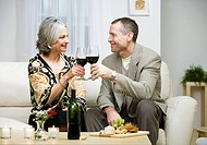 Mature couple toasting with wine in living room