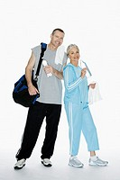 Mature couple in sportswear against white background, portrait