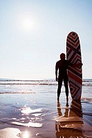 Man standing on beach with surfboard