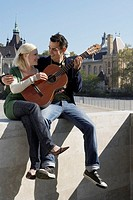 Couple playing guitar outdoors smiling