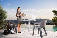 Woman at patio table working by infinity pool