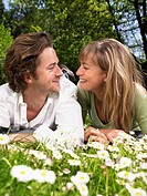 Couple lying in the grass smiling at each other