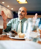 Man sitting at table in restaurant, gesturing