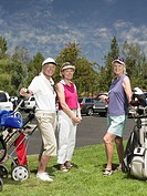 Three mature women with golf bags standing on golf course, portrait